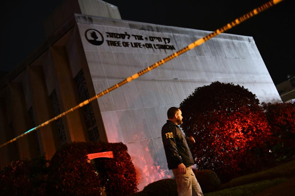 An FBI agent stands behind a police cordon outside the Tree of Life Synagogue after a shooting there left 11 people dead in the Squirrel Hill neighborhood of Pittsburgh on October 27, 2018. The shooting was the deadliest anti-Semitic attack in recent American history. (Brendan Smialowski / AFP via Getty Images)