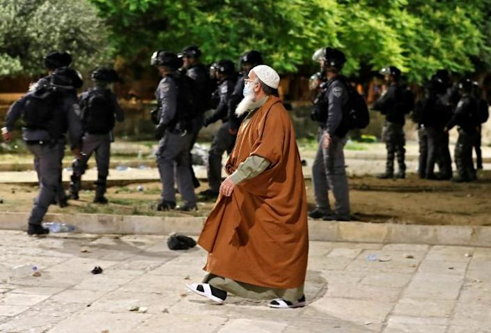 A Palestinian man walks by amid clashes between Israeli security forces and Palestinian protesters at the al-Aqsa mosque compound
