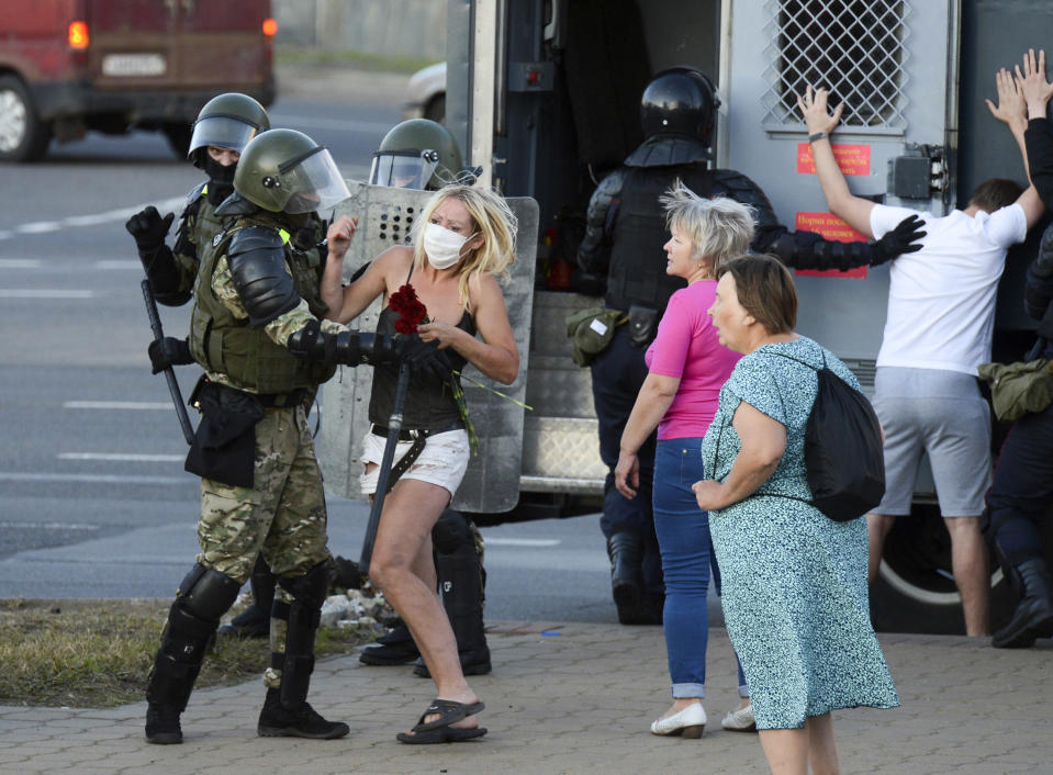 FILE - In this file photo taken on Tuesday, Aug. 11, 2020, a woman fights with a police officer in the capital of Minsk, Belarus, as others detain protesters following a disputed presidential election. Hundreds of people released from custody after a violent crackdown on protests in Belarus are sharing their accounts of harsh treatment at the hands of police. (AP Photo, File)