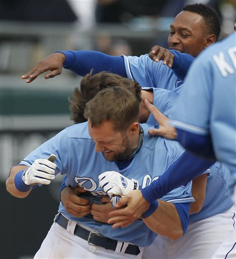 Kansas City Royals' Alex Gordon, bottom, is congratulated by teammates including Jarrod Dyson, top, after his winning RBI single that scored Lorenzo Cain in the 10th inning of a baseball game against the Chicago White Sox at Kauffman Stadium in Kansas City, Mo., Sunday, May 5, 2013. The Royals won 6-5. (AP Photo/Colin E. Braley)