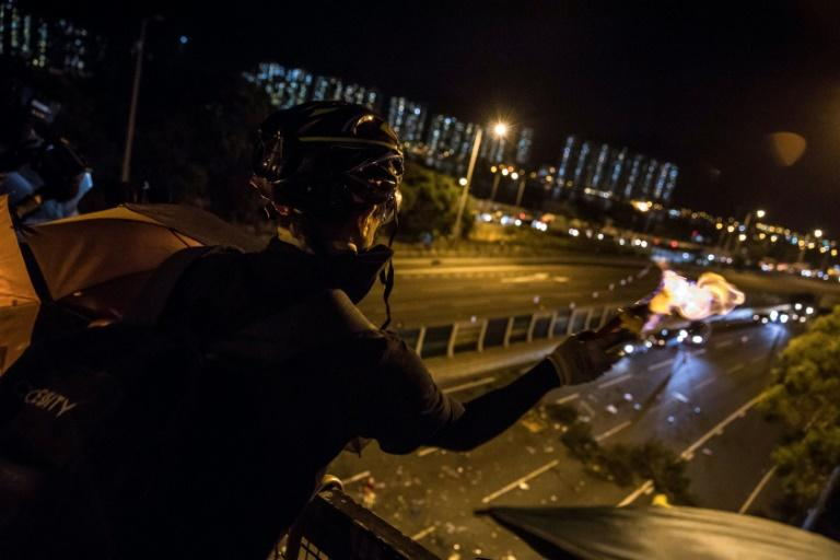 A protester throws a Molotov cocktail to stop vehicles from passing through their roadblock beneath a bridge at the Chinese University of Hong Kong