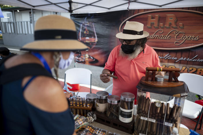 Tourists look at cigars for sale at the Old San Juan dock after the arrival of Carnival's Mardi Gras cruise ship in San Juan, Puerto Rico, Tuesday, Aug. 3, 2021, marking the first time a cruise ship visits the U.S. territory since the COVID-19 pandemic began. (AP Photo/Carlos Giusti)