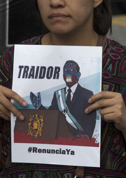 """A woman holds a poster showing a cartoon image of Guatemalan President Jimmy Morales with the word """"traitor"""" ,during a press conference organized by civil society groups in front of the Constitutional Court in Guatemala City, Friday, July 26, 2019. The Trump administration signed an agreement with Guatemala Friday that will restrict asylum applications to the U.S. from Central America. (AP Photo/ Oliver de Ros)"""