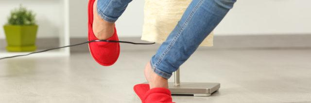 woman's legs tripping over an electrical cord at home