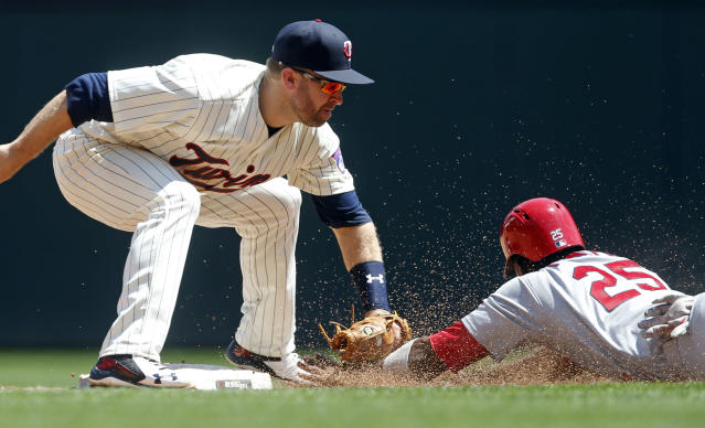 Minnesota Twins' second baseman Brian Dozier tags out St. Louis Cardinals' Dexter Fowler during a steal attempt in the third inning of a baseball game Wednesday, May 16, 2018, in Minneapolis. (AP Photo/Jim Mone)