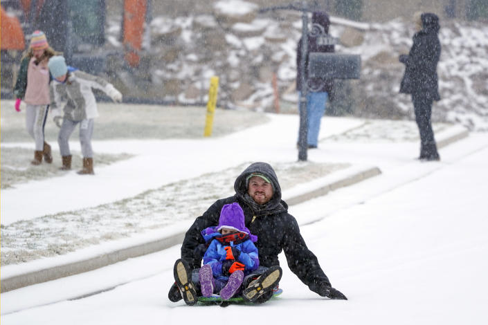 Andy German and Lyla, 6, sled down an icy street Monday, Feb. 15, 2021, in Nolensville, Tenn. Much of Tennessee was hit with a winter storm that brought freezing rain, snow, sleet and freezing temperatures. (AP Photo/Mark Humphrey)