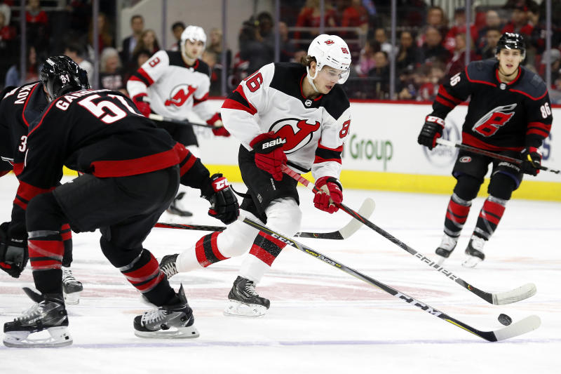 New Jersey Devils' Jack Hughes (86) moves the puck past Carolina Hurricanes' Jake Gardiner (51) during the first period of an NHL hockey game in Raleigh, N.C., Friday, Feb. 14, 2020. (AP Photo/Karl B DeBlaker)