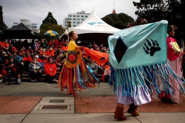 People watch Tsartlip dancers perform during a ceremony Thursday at Victoria's Centennial Square to honour victims and survivors of the residential school system.  (Chad Hipolito/The Canadian Press - image credit)