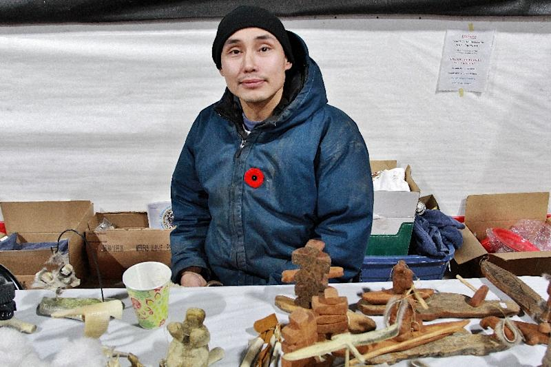 Local carver Jonathan C. Elias sells his wares during celebrations for the opening of the new highway to Tuktoyaktuk (AFP Photo/Melinda TROCHU)