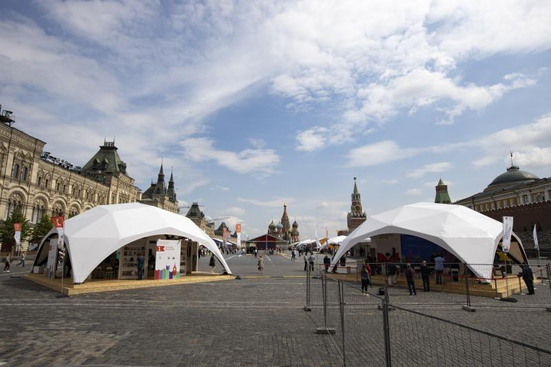 Outdoor book markets under tents are set up at Red Square with GUM, left, St. Basil's Cathedral, center, Spasskaya Tower, second with, and the Kremlin Wall, right, in Moscow, Russia, Saturday, June 6, 2020. Muscovites clad in face masks and gloves ventured into Red Square for an outdoor book market, a small sign of the Russian capital's gradual efforts to open up amid coronavirus concerns. (AP Photo/Alexander Zemlianichenko)