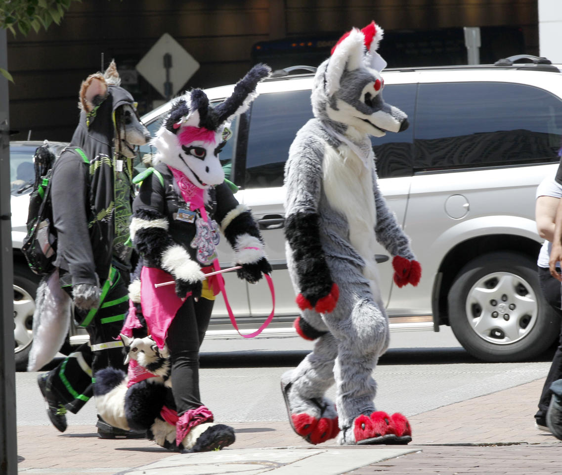 In this photo made on Thursday, June 14, 2012, people in animal costumes walk down Penn Ave. near the David Lawrence Convention Center in Pittsburgh. Anthrocon, the world's largest convention for people who dress and assume the rolls of fictional animal characters, is back in its adopted home with an expected 5,000 participants between June 14 to 17, 2012. (AP Photo/Keith Srakocic)