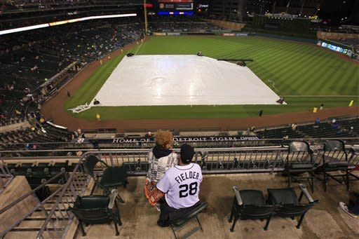 Jim and Debbie Michalski sit through a rain delay before a baseball game between the Minnesota Twins and the Detroit Tigers at Comerica Park in Detroit, Friday, Sept. 21, 2012. (AP Photo/Carlos Osorio)