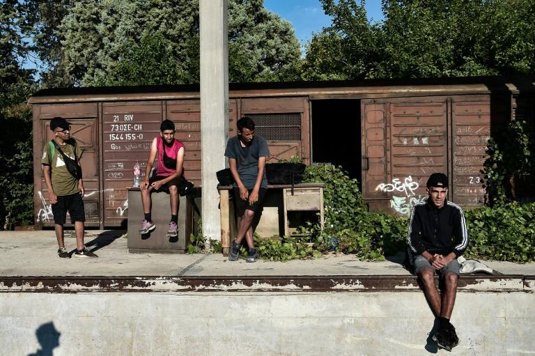 Migrants sleep in disused railway wagons and wait for the chance to hitch a ride on a train
