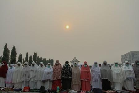 Indonesian Muslim women pray for rain during a long drought season and haze in Pekanbaru