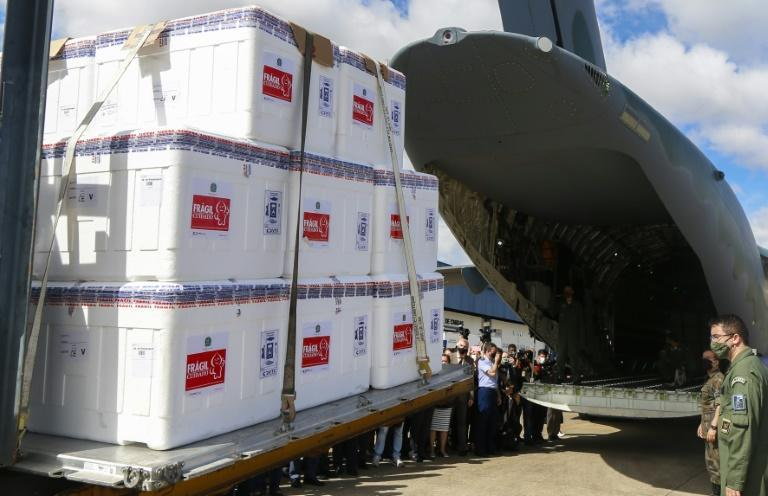 Brazilian soldiers load CoronaVac vaccine doses into a military plane at Guarulhos airport in Sao Paulo for distribution across the country on January 18, 2021
