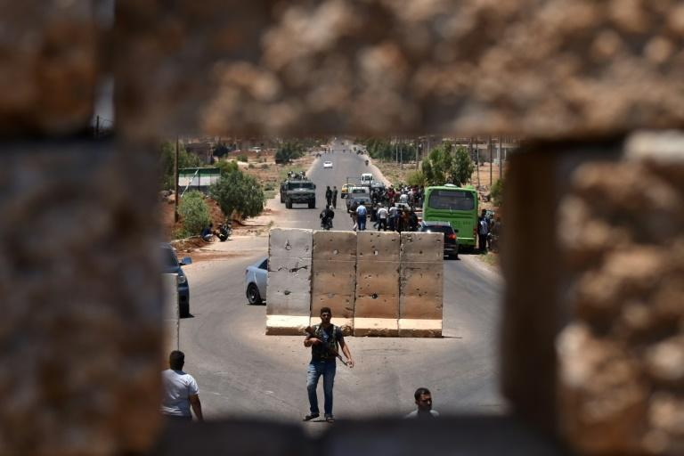 A bus stops at a checkpoint as displaced Syrians return to their hometown of Bosra al-Sham, in southwestern Syria's Daraa province, on July 11, 2018