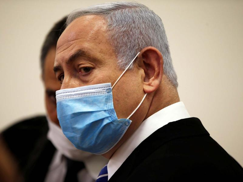 Benjamin Netanyahu, wearing a face mask, looks on while standing inside the court room as his corruption trial opens: REUTERS