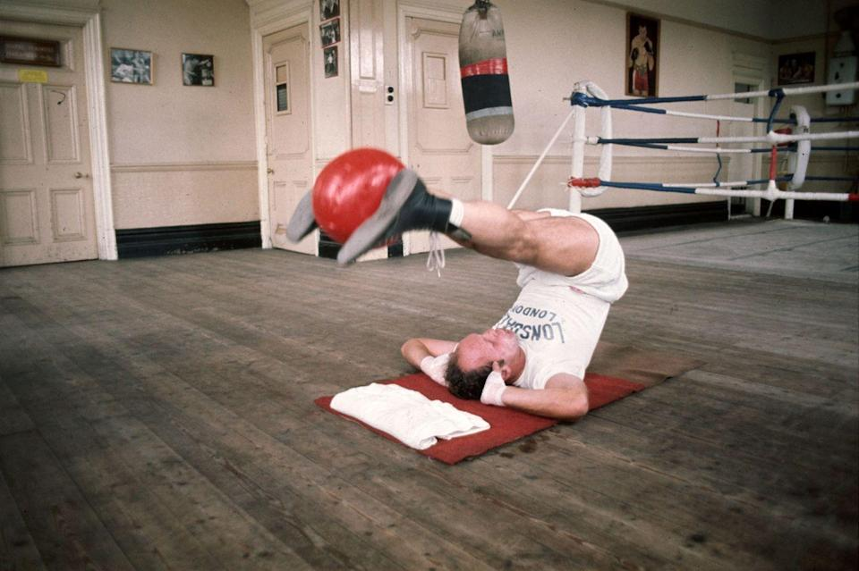 <p>Heavyweight boxer, Henry Cooper, uses the medicine ball for a killer ab exercise. </p>