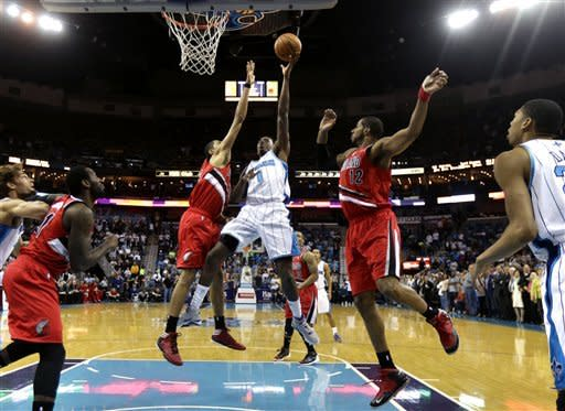 New Orleans Hornets forward Al-Farouq Aminu (0) shoots between Portland Trail Blazers forward LaMarcus Aldridge (12) and forward Nicolas Batum, left, in the first half of an NBA basketball game in New Orleans, Sunday, March 10, 2013. (AP Photo/Gerald Herbert)