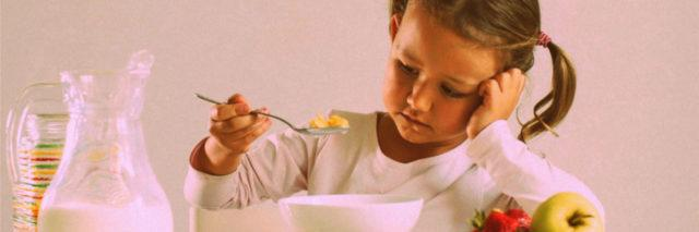 Little girl looking distastefully at cereal bowl