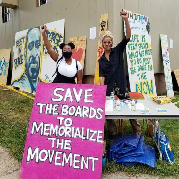 PHOTO: Leesa Kelly and Kenda-Zellner Smith pose with protest art they collected thought Save the Boards to Memorialize the Movement in Minneapolis. Protest art has been collected by Save the Boards to Memorialize the Movement. (Courtesy of Save the Boards to Memorialize the Movement)