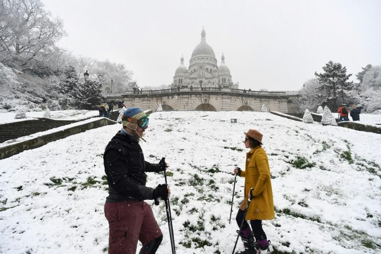 A couple prepare to ski on the snow-covered Montmartre hill in Paris