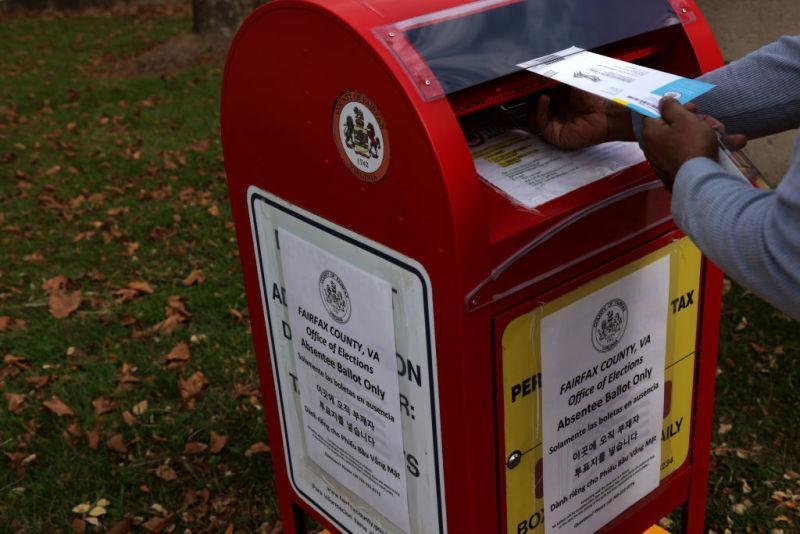 A voter drops off an absentee ballot for the November 3, 2020 elections into a collecting bin outside Fairfax County Government Center on October 19, 2020 in Fairfax, Virginia.