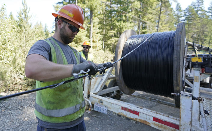 FILE - In this Wednesday, Aug. 4, 2021, file photo, Skylar Core, right, a worker with the Mason County (Wash.) Public Utility District, installs a hanger onto fiber optic cable as it comes off of a spool, while working with a team to install broadband internet service to homes in a rural area surrounding Lake Christine near Belfair, Wash. (AP Photo/Ted S. Warren, File)