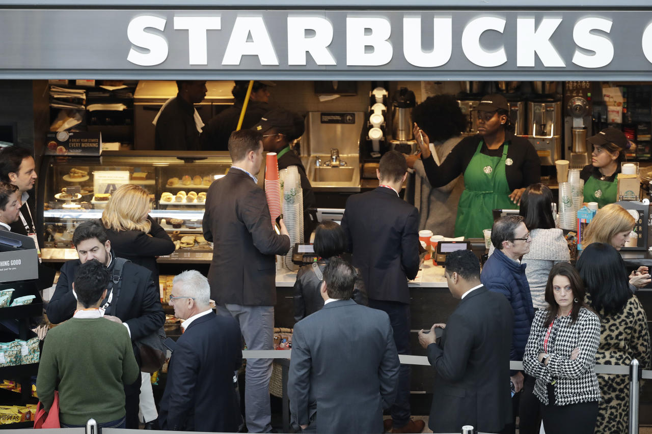 People line up to shop at a Starbucks, Sunday, Jan. 14, 2018, in New York. (AP Photo/Mark Lennihan)