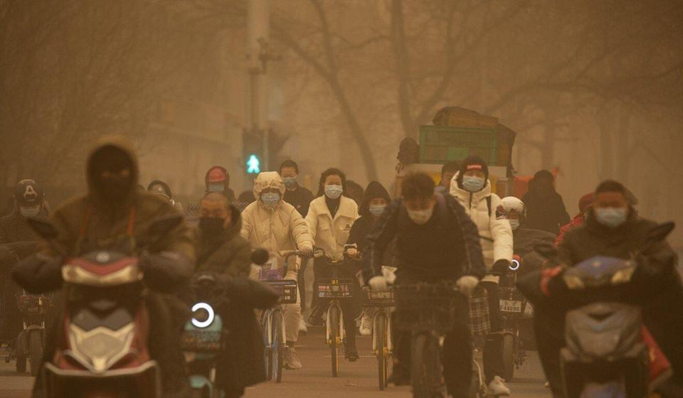 Commuters during Beijing's morning rush hour as the worst sandstorm in a decade sends air pollution soaring on Monday. Photo: AP