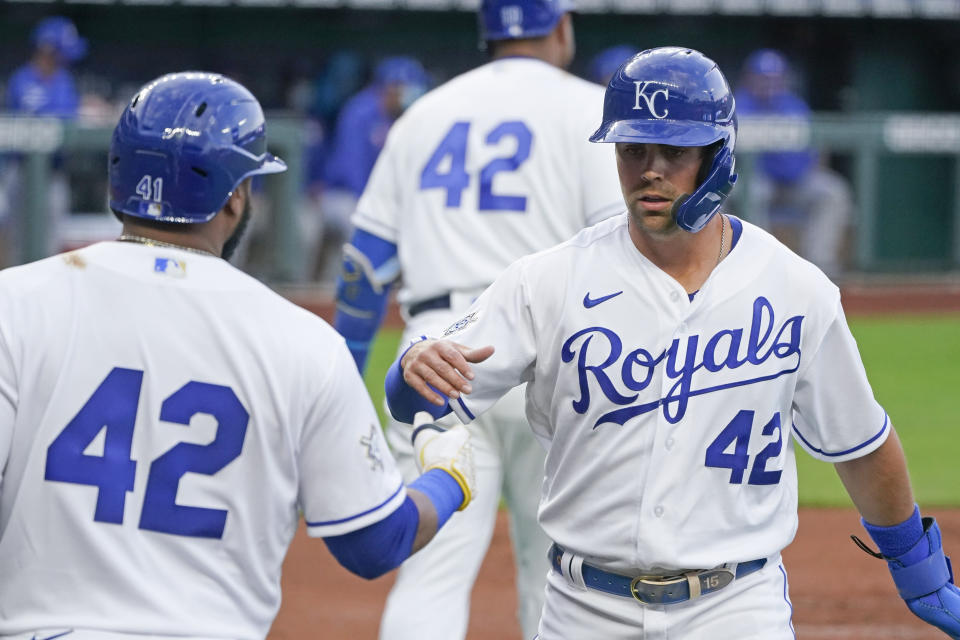 Kansas City Royals' Whit Merrifield, right, celebrates with Carlos Santana after he scored on a double by Andrew Benintendi during the first inning of a baseball game against the Toronto Blue Jays Thursday, April 15, 2021, in Kansas City, Mo. (AP Photo/Charlie Riedel)