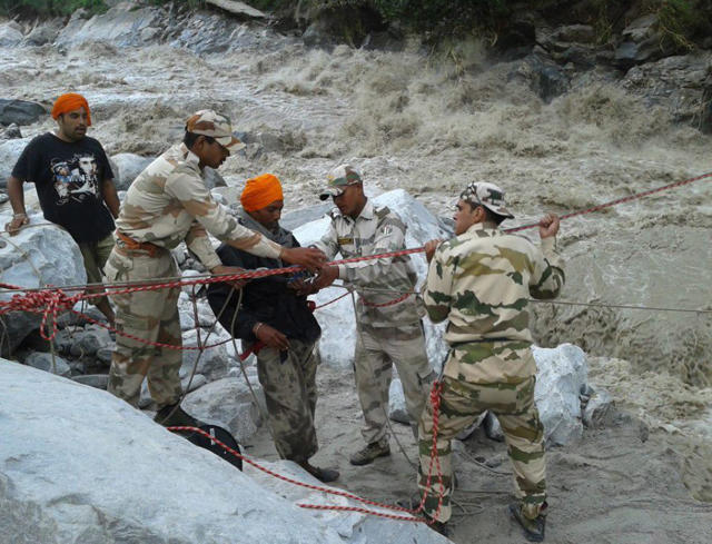 "In this handout photograph released by the Indo-Tibetan Border Police (ITBP) on June 21, 2013, ITBP personnel prepare to maneuver a flood evacuee across a raging river in Ghangaria following heavy rain in the region. Rescue workers recovered scores of bodies from the Ganges river in northern India on June 21, as the death toll from flash floods and landslides topped 200, with thousands of mainly pilgrims and tourists still stranded. Floods and landslides from monsoon rains have also struck across the border in Nepal, leaving at least 39 people dead, the government there said. AFP PHOTO/ITBP ----EDITORS NOTE---- RESTRICTED TO EDITORIAL USE - MANDATORY CREDIT - ""AFP PHOTO/ITBP"" - NO MARKETING NO ADVERTISING CAMPAIGNS - DISTRIBUTED AS A SERVICE TO CLIENTS -----"