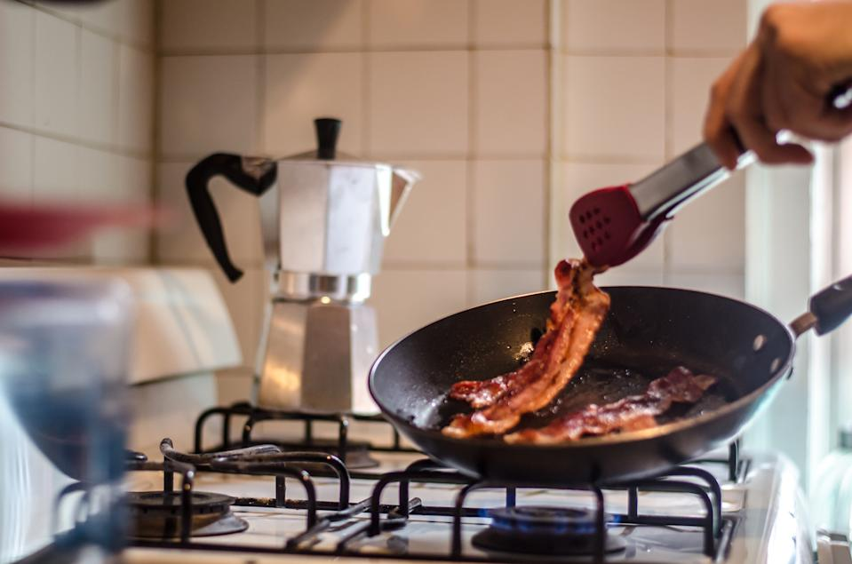 A person cooks bacon in a pan.