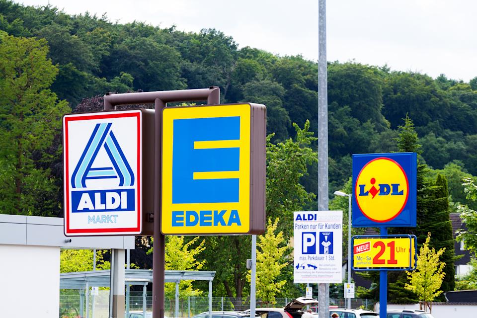 Essen, Germany - June 21, 2014: Capture of logos and signs of three German big discounters close together, seen from shared parking space in Essen Kettwig. There are logos of Aldi North, Edeka and Lidl.