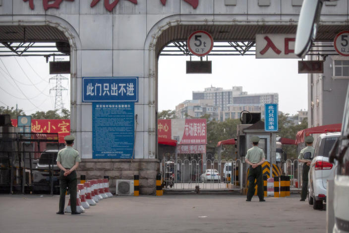 Chinese paramilitary police stand guard at barricaded entrances to the Xinfadi wholesale food market district in Beijing, Saturday, June 13, 2020. Beijing closed the city's largest wholesale food market Saturday after the discovery of seven cases of the new coronavirus in the previous two days. (AP Photo/Mark Schiefelbein)