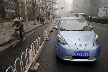 A Roewe E50 electric car is parked next to a street as a bicycle travels past amid heavy smog in Beijing