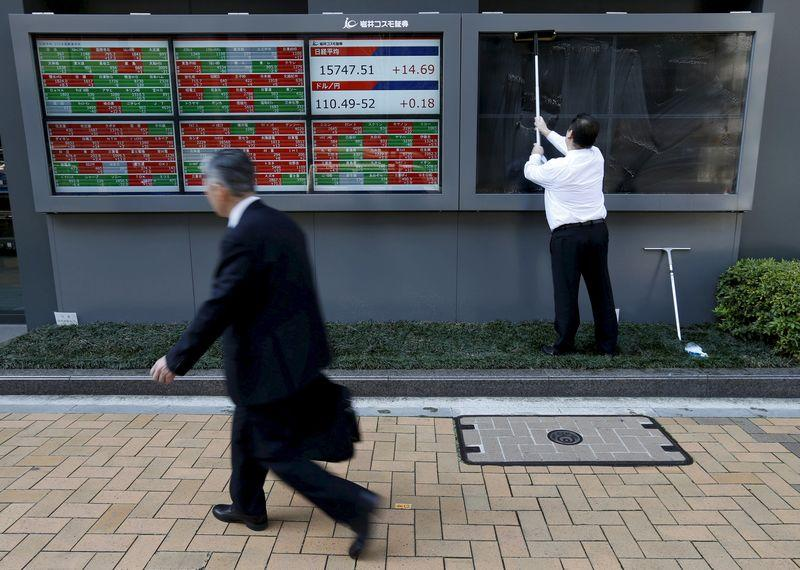 A man (R) cleans electronic boards showing Japan's Nikkei average, the exchange rate between the Japanese yen against the U.S. dollar and stock quotation outside a brokerage in Tokyo, Japan, in this April 6, 2016 file photo. REUTERS/Issei Kato/Files