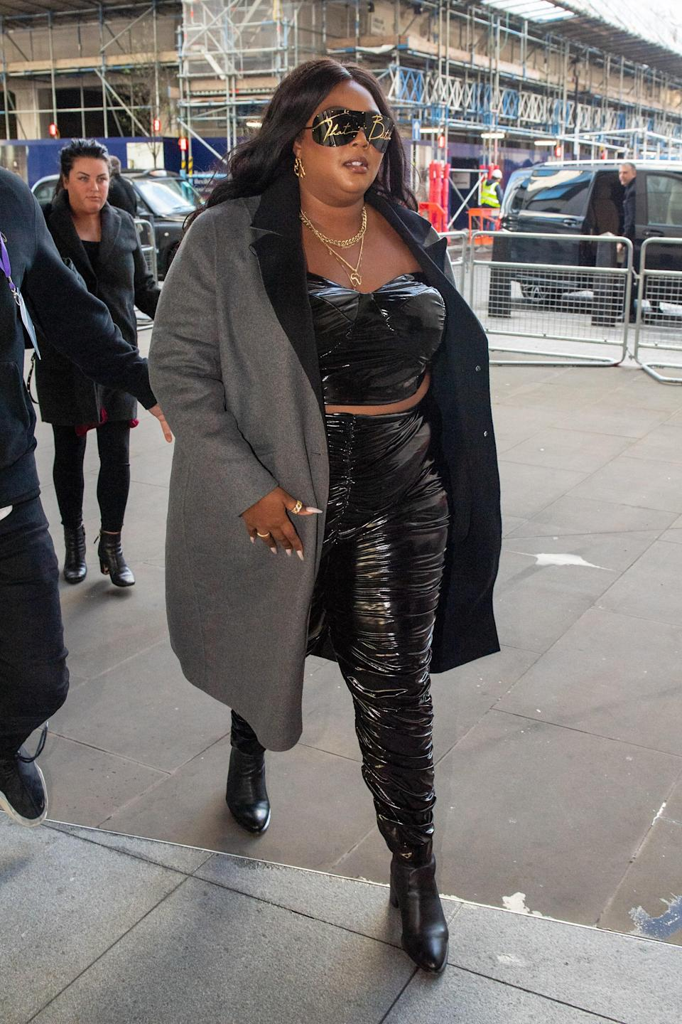 """Lizzo never misses the opportunity to make a fashion statement when she's on UK soil. For her appearance on BBC's Radio 1's Live Lounge, she donned black and gold sunglasses that were emblazoned with the words """"That Bitch."""""""