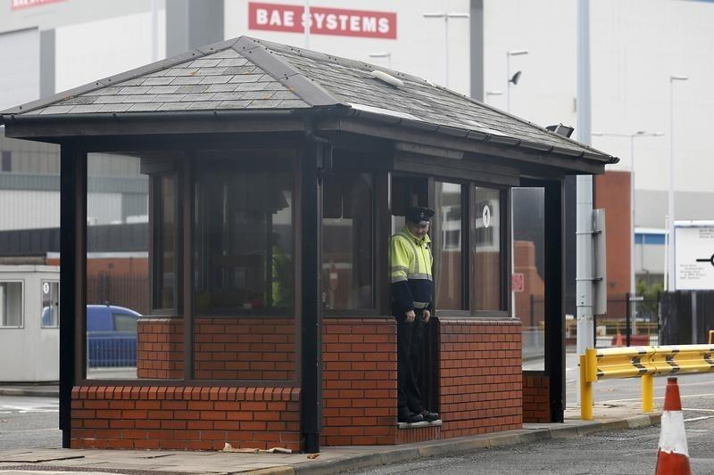 A security guard stands at the entrance to the naval dockyards, where BAE Systems is located, in Portsmouth