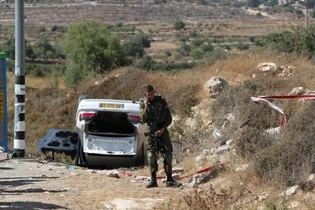 An Israeli soldier stands near the scene of what Israeli military said is a car-ramming attack near the settlement of Elazar in the Israeli-occupied West Bank