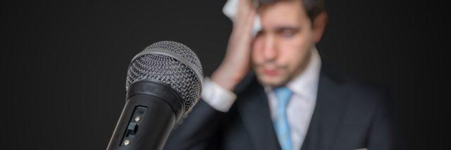 a microphone placed in front of a nervous man about to give a public speech
