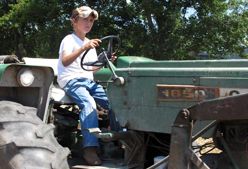 In a June 20, 2012, photo ten-year-old Jacob Mosbacher guides a tractor through a bean field on his grandparents' property near Fults, Ill. Agriculture organizations and federal lawmakers from farm states succeeded last spring in convincing the U.S. Labor Department to drop proposals limiting farm work by children such as Jacob, whose parents say such questions of safety involving kids should be left to parents. (AP Photo/Jim Suhr)