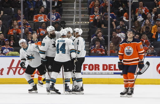 San Jose Sharks celebrate a goal as Edmonton Oilers' Matthew Benning (83) skates past during the second period of an NHL hockey game Thursday, April 4, 2019, in Edmonton, Alberta. (Jason Franson/The Canadian Press via AP)