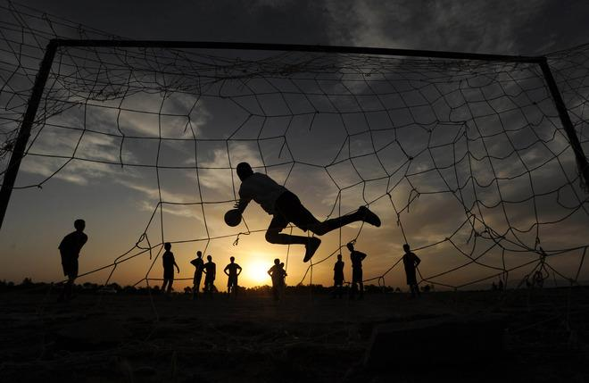 TOPSHOTS Afghan youth play football in the evening in the city of Herat on May 19, 2012. AFP PHOTO/ Aref KarimiAref Karimi/AFP/GettyImages