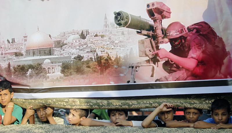Palestinian boys look on from behind a stage where a giant poster showing a Hamas military wing fighter is displayed during a demonstration on August 17, 2014 (AFP Photo/Said Khatib)