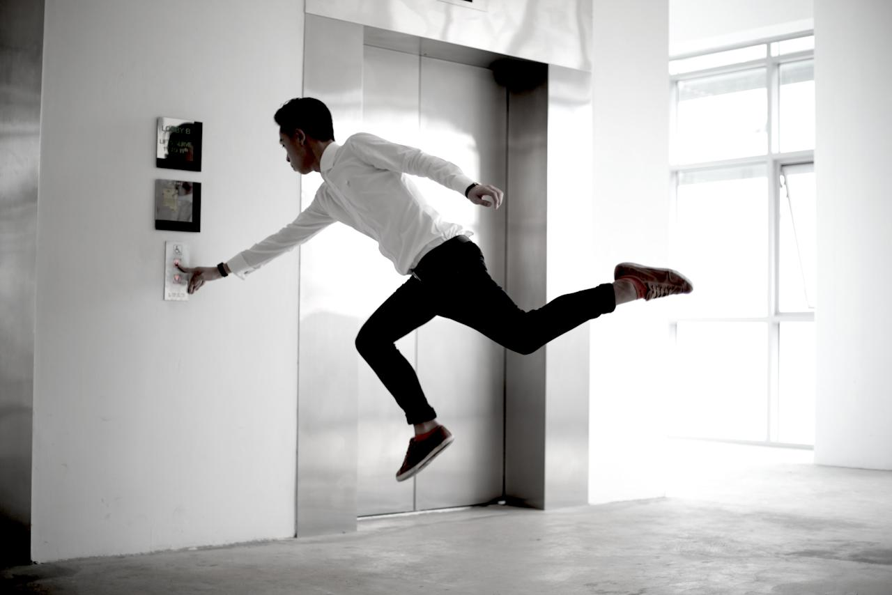 A sharply dressed man presses the button for the lift. Wouldn't it be quicker to fly down? (Levitation SG/ Rex Features)
