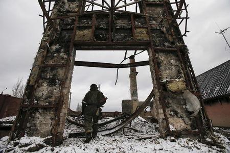 A member of the armed forces of the separatist self-proclaimed Donetsk People's Republic walks near a building destroyed during battles with the Ukrainian armed forces in Vuhlehirsk, Donetsk region, Ukraine, in this February 4, 2015 file photo. REUTERS/Maxim Shemetov/Files