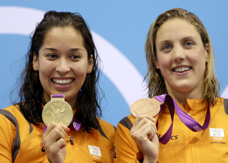Netherlands' Ranomi Kromowidjojo, left, holds her gold medal as her compatriot Marleen Veldhuis holds her bronze medal at the medal ceremony for the women's 50-meter freestyle at the Aquatics Centre in the Olympic Park during the 2012 Summer Olympics in London, Saturday, Aug. 4, 2012. (AP Photo/Michael Sohn)