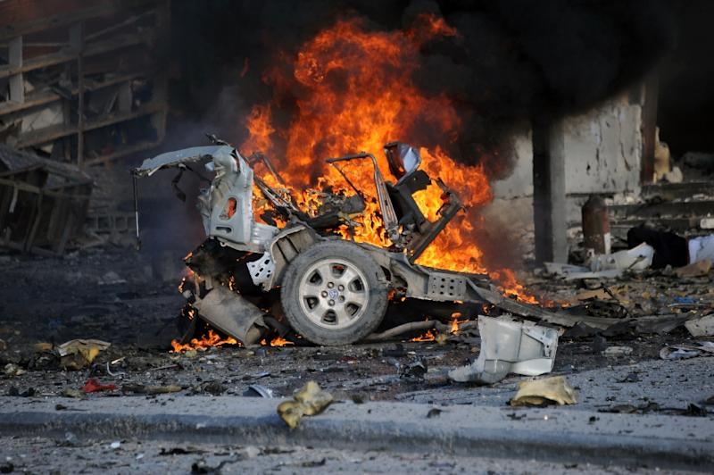 A burning car near the damaged Sahafi hotel in Mogadishu on November 1, 2015 after an explosion (AFP Photo/Mohamed Abdiwahab)