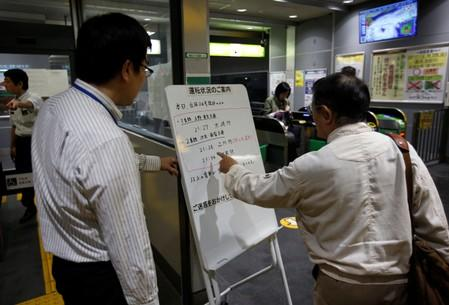 A passenger checks a message board announcing last train services ending earlier due to Typhoon Trami, at East Japan Railway Company's station in Tokyo